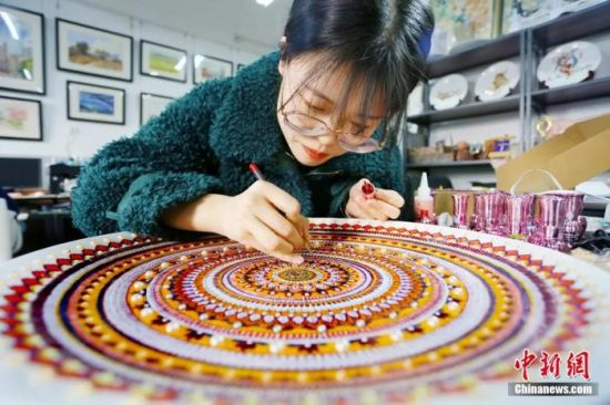 图为学生用指甲油制作敦煌彩绘工艺盘。