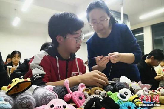 图为老师指导学生织钥匙包。