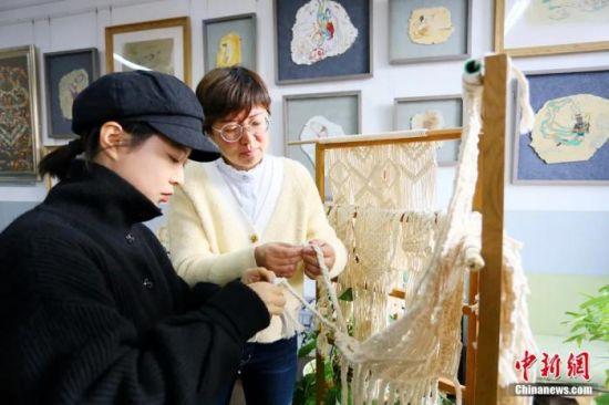图为老师指导学生编织壁饰。