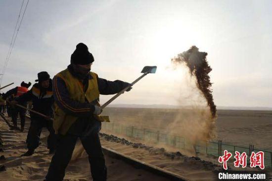 铁路职工在清沙现场。 刘勃 摄