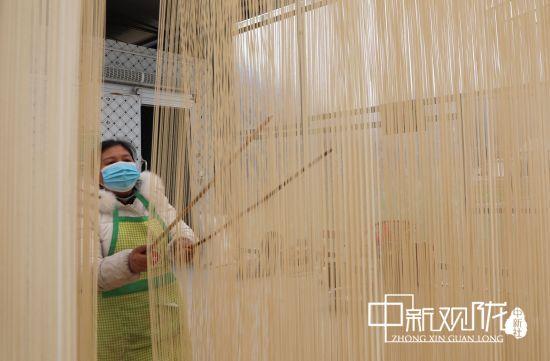 成县苏元镇张湾村群众在对晾晒的手工挂面开架。 刘敏 摄