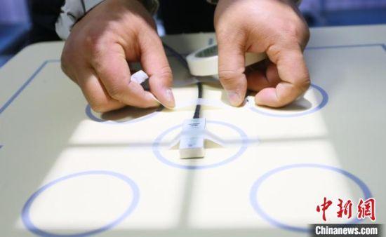 """图为甘肃秦洲核与辐射安全技术有限公司专业技术人员粘贴检测探头,为医疗设备""""体检""""。 高展 摄"""