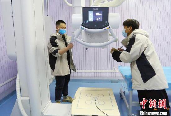图为民用核技术应用设备检测员检测医疗设备,并记录相关数据。 高展 摄