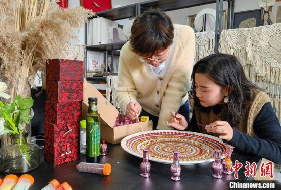 图为老师指导学生制作敦煌彩绘工艺盘。 刘玉桃 摄