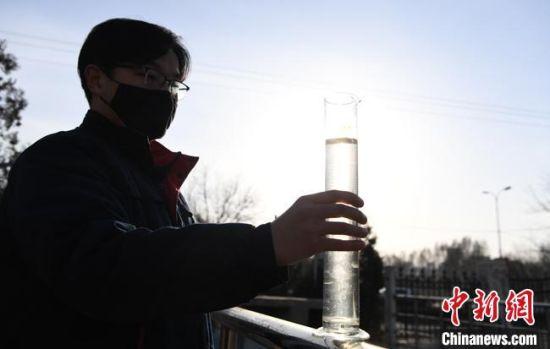 兰州市七里河安宁污水处理厂工作人员用玻璃器皿盛出经过处理的污水,它清澈无异味,仅有少许肉眼可见颗粒。 杨艳敏 摄