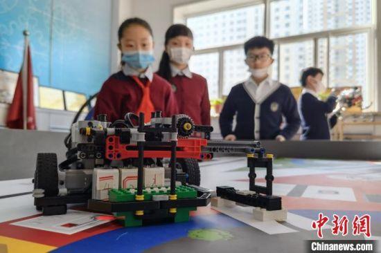 图为学生自己编程语言、搭建以及制作运行机器人。 刘玉桃 摄