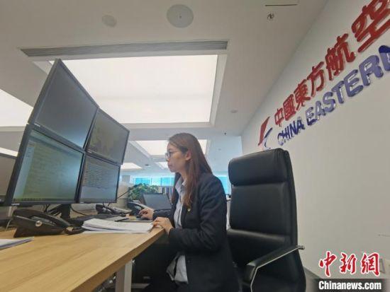 图为指挥长胡兰萍查看各航线数据信息。 张婧 摄