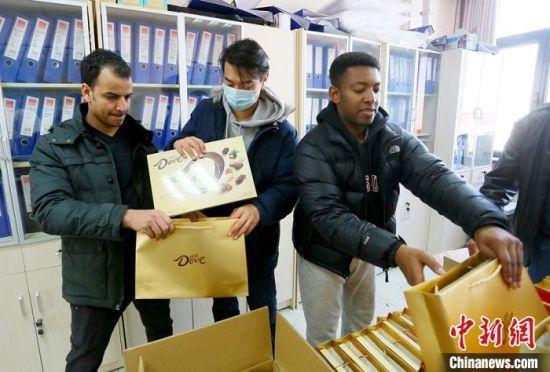 """该校留学生马弈、阿布、王山木(从左至右)协助老师为留学生发放""""春节大礼包""""。 高展 摄"""