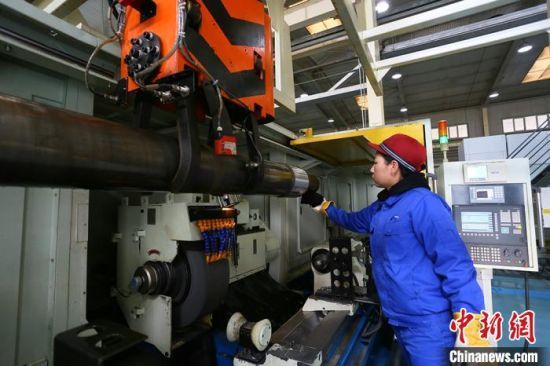 中国铁路兰州局集团有限公司兰州西车辆段轮轴装修工刘晓燕操控机床打磨轮轴。  高展 摄