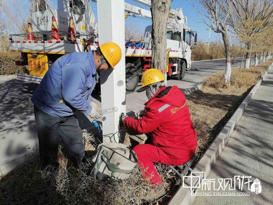 图为市政工人正在检修路灯。 聂春霞 摄