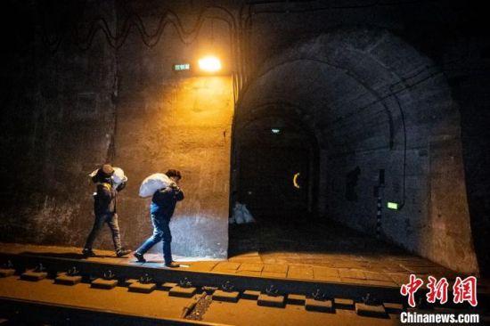 """图为苗琦与工友用编织袋将碎冰""""打包"""",运往100米开外的横通道内。 李童辉 摄"""