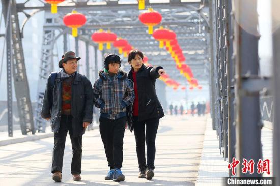 2021年春节期间,台湾商人杜书亿一家三口走过挂满火红灯笼的兰州中山铁桥。 中新社记者 高展 摄