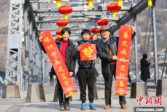 2021年春节期间,台湾夫妻杜书亿和王梅芬带着孩子一起在兰州中山铁桥前合影留念。 中新社记者 高展 摄