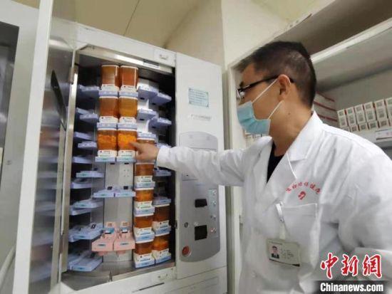 图为在住院部药房工作8年时间的主管药剂师杨天才向记者展示全自动片剂摆药机。 张婧 摄