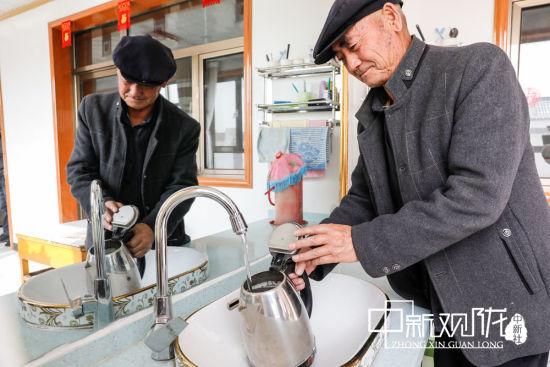 图为古浪县干城乡富民新村村民徐生喜正在接自来水。(资料图)
