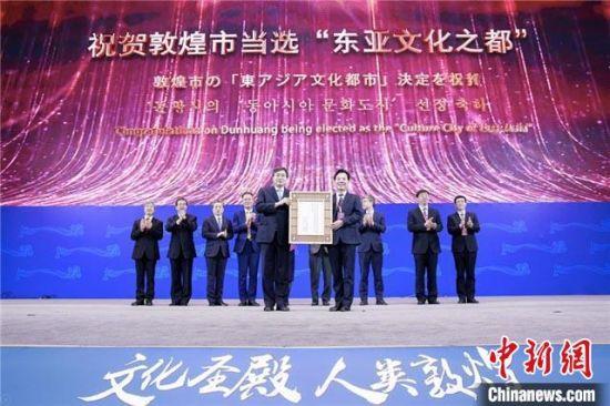 """开幕式上,敦煌市被颁授2021""""东亚文化之都""""纪念牌。 甘肃省文化和旅游厅供图"""