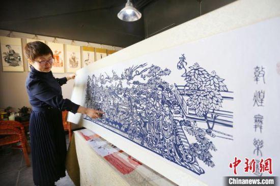 4月下旬,庄生娟向记者介绍耗时两个月的剪纸作品《敦煌舞乐图》。 高展 摄