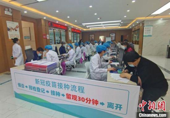 图为城关区雁南街道社区卫生服务中心接种点,医护人员登记、录入接种人员的信息。 闫姣 摄