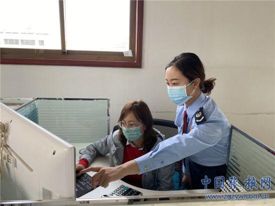税务人员正在辅导高台县金康脱水蔬菜有限公司通过新系统办理备案信息变更。
