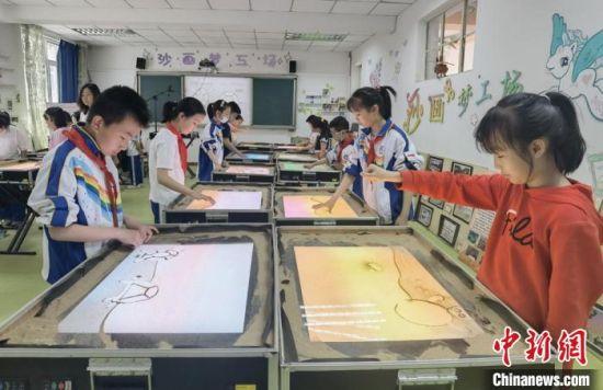 """为七里河小学""""沙画课堂""""。 高展 摄"""