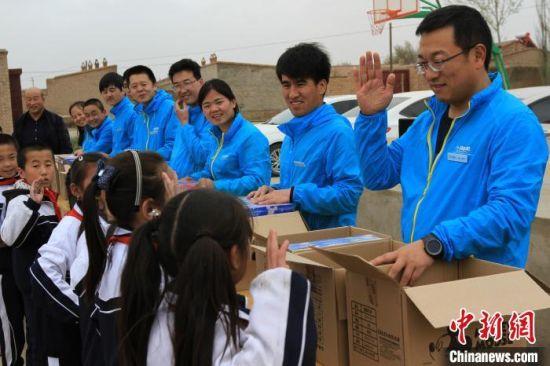 朱社会(右)每年都带领员工去贫困山区捐书。(资料图) 受访者供图
