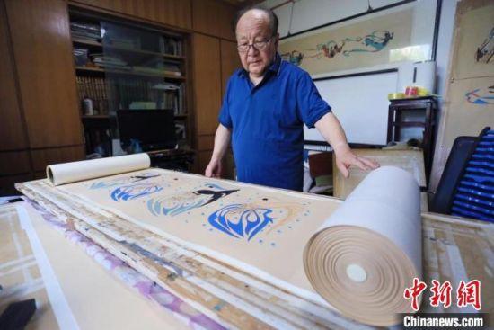 图为范兴儒展示他最珍视的《八十七飞天卷》,耗时5年所作,画卷长50米,包含87身代表飞天。 高展 摄