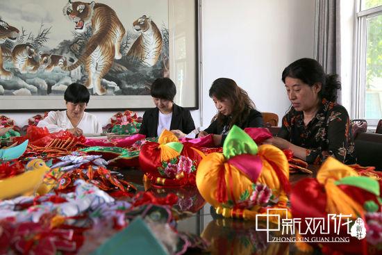 庆阳锦篮文化传播有限公司组织绣娘在生产基地赶制香包 。
