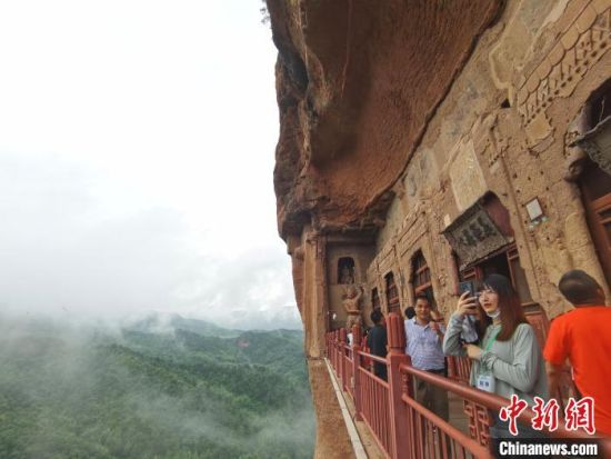 """图为游人拍摄麦积山石窟风景区""""仙境""""。 张婧 摄"""