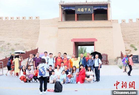 游客在嘉峪关关城前合影留念。高展 摄