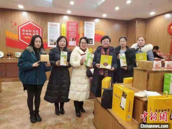 图为刘军梅(左三)和同事展示农产品。(资料图) 受访人供图