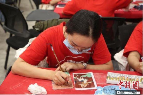 图为青年学子体验敦煌泥版画,了解敦煌壁画制作工艺。 信晓泽 摄