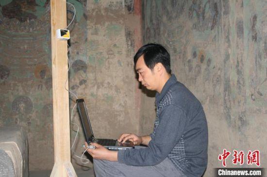 图为2004年杜建君在洞窟内下载温湿度数据。(资料照片) 敦煌研究院供图