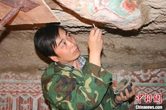 图为2005年杜建君在洞窟内工作。(资料照片) 敦煌研究院供图