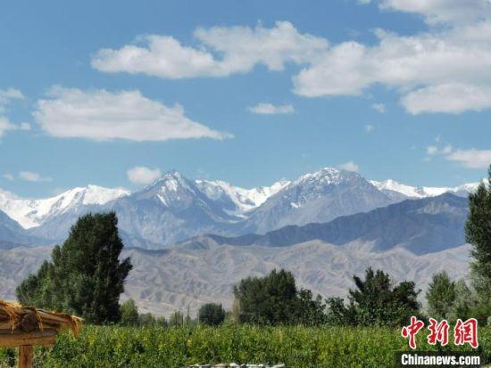 7月下旬,酒泉市肃州区祁连山覆盖白雪与蓝天白云相映成趣。(资料图) 张婧  摄