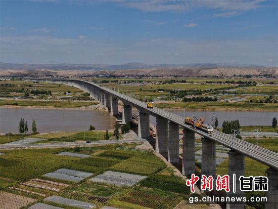 图为中铁电气化局建设者正在靖远黄河特大桥架设首条接触网导线 李向奥摄
