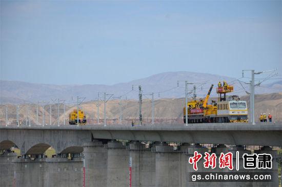 图为中铁电气化局建设者正在靖远黄河特大桥架设首条接触网导线。李向奥 摄
