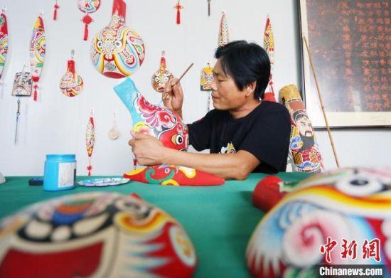 9月初,在甘肃省陇南市徽县,马勺脸谱的省级传承人马龙在工作室内绘制脸谱。 高展 摄