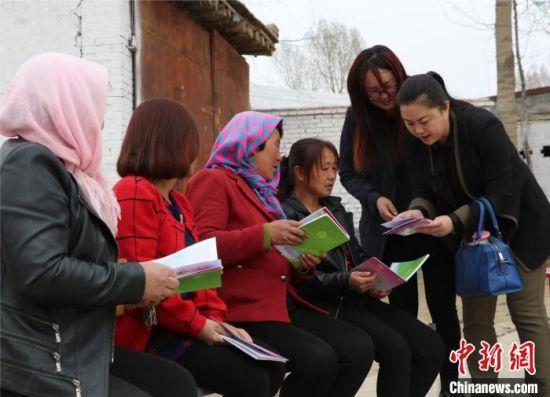 """图为妇联干部为农村妇女讲解""""两癌""""防治知识。(资料图) 甘肃省政府妇儿工委办供图"""