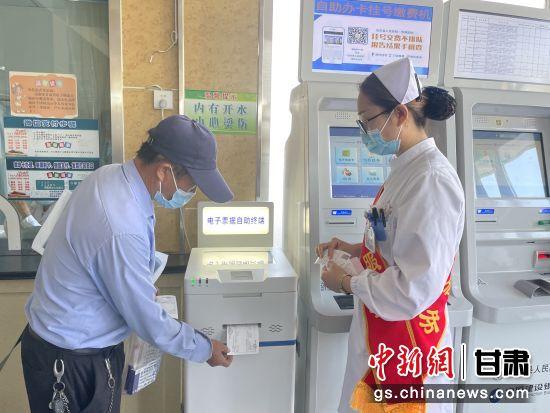 图为,患者在瓜州县人民医院电子票据终端机上自助打印票据。
