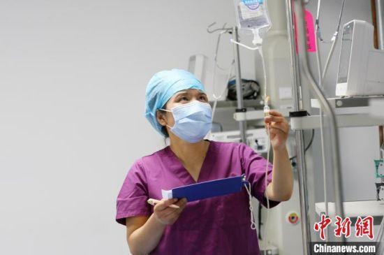 图为脱亚莉在为病人做护理。 高展 摄