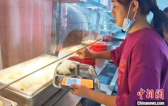 图为学生自助取餐,按克缴费避免浪费。 史静静 摄