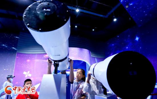 9月11日,甘肃省张掖市临泽县的小学生在张掖科技馆体验高倍望远镜的魅力。