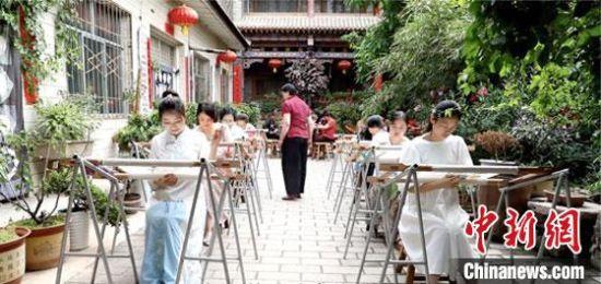 图为刘兰芳(红衣者)把香包做成产业,为当地妇女提供就业机会。(资料图) 张煜琛 摄
