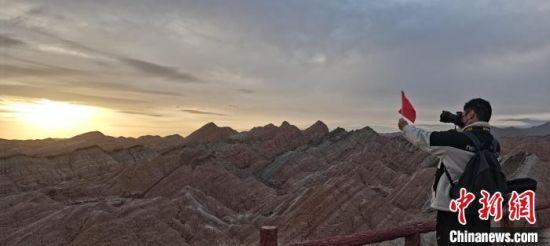 图为张掖丹霞景区游客观日出拍照留念。