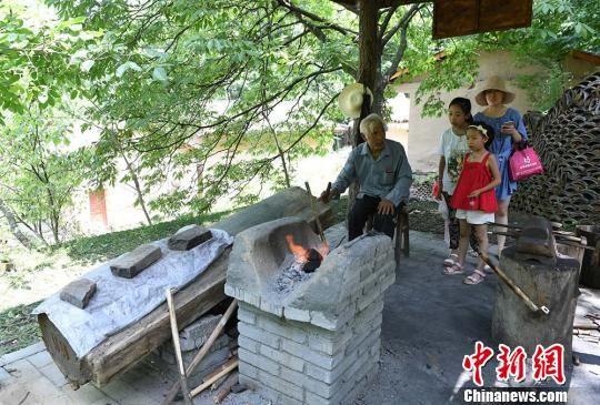图为康县岸门口镇街道村朱家沟社,在这个旅游村里,有一个简易铁匠铺,老人在这里打铁。 杨艳敏 摄