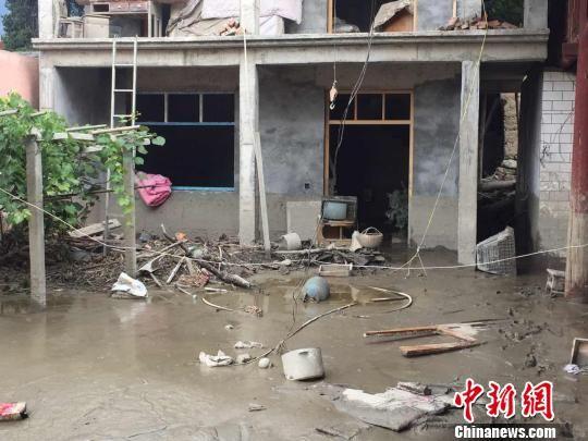 图为泥石流灾祸后,有些农户家里的电视、饭桌等扔在院里,屋内积满淤泥,受灾民众已无法回到家里。 南如卓玛 摄