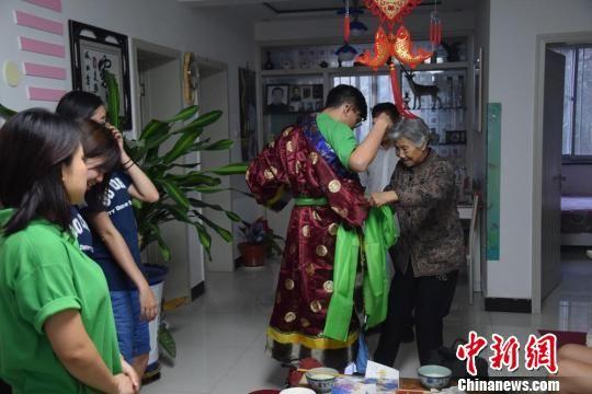 图为参访学生在肃南县祁丰藏族乡试穿藏族服饰。 陈素怡 摄