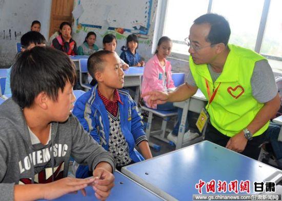图为甘肃经济动员心理干预服务大队队员为孩子们作心理疏导。