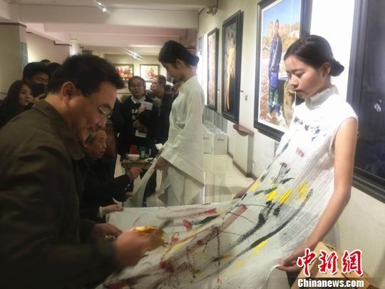 10月18日下午,王秀章携手五名甘肃籍画家在模特服装上手绘,创造了一系列含有我国元素的的画作。 史静静 摄