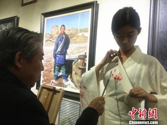 图为10月18日下午,画家现场在模特的服装上创造手绘著作。 史静静 摄